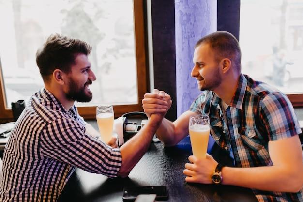 Koncepcja ludzi, mężczyzn, wypoczynku, przyjaźni i świętowania - szczęśliwi przyjaciele płci męskiej piją piwo i walczą na ręce w pubie