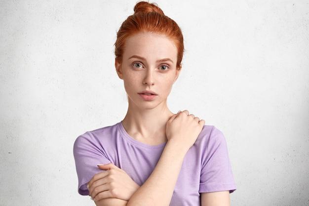 Koncepcja ludzi, mimiki i emocji. urocza, piegowata, rudowłosa modelka ma zawiązane włosy, ubrana w zwykły strój
