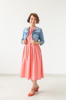 Koncepcja ludzi, mody i stylu - młoda kobieta pozuje w ubraniach w studio na białej ścianie