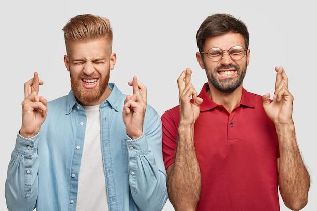 Koncepcja ludzi, mowa ciała i życzenia. marzycielski brodaty młody mężczyzna biodrówki zaciska zęby i skrzyżowane palce, stoi blisko, ma nadzieję, że marzenia się spełniają, mają specyficzny wygląd, odizolowany na białej ścianie