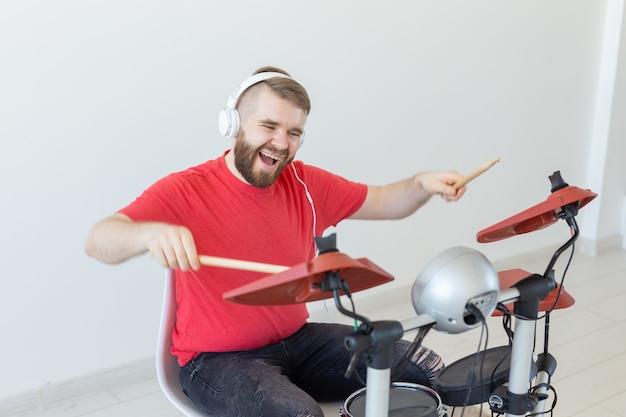 Koncepcja ludzi, muzyki i hobby - człowiek z białymi słuchawkami grający na bębnach ustawionych na jasnej ścianie.