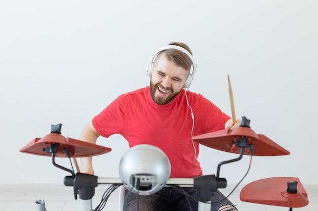 Koncepcja ludzi, muzyki i hobby - człowiek z białymi słuchawkami grający na bębnach ustawionych nad światłem