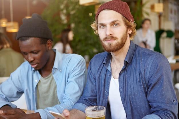 Koncepcja ludzi, nowoczesny styl życia, przyjaźń, relacje i technologie. dwóch przystojnych, stylowych mężczyzn odpoczywa w kawiarni lub barze, pije piwo i miło spędza czas korzystając z bezpłatnego wi-fi w telefonach komórkowych