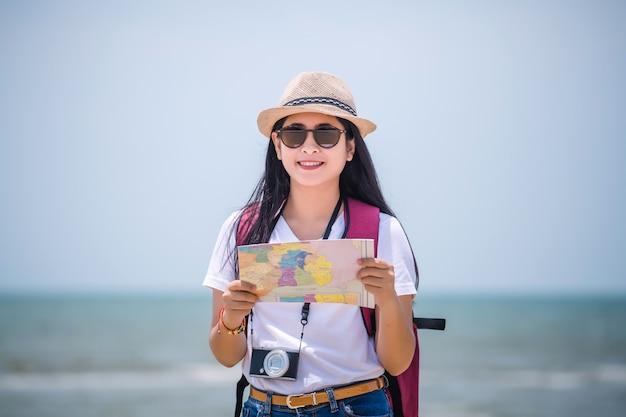 Koncepcja ludzi podróżujących. młody szczęśliwy azjatykci gril przy plażą