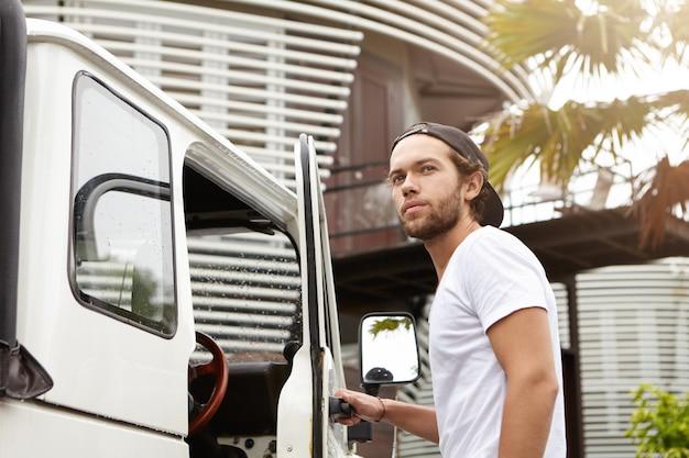 Koncepcja ludzi, przyrody i transportu. młody hipster uśmiechając się radośnie, otwierając drzwi swojego białego pojazdu terenowego