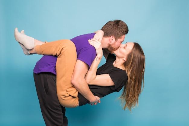 Koncepcja ludzi, relacji i zabawy - uśmiechnięty mężczyzna trzyma piękną kobietę na niebieskiej ścianie