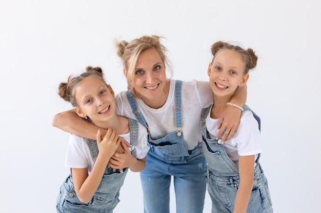 Koncepcja ludzi, rodziny i dzieci - portret pięknej matki obejmującej córki bliźniaczki na białej powierzchni.