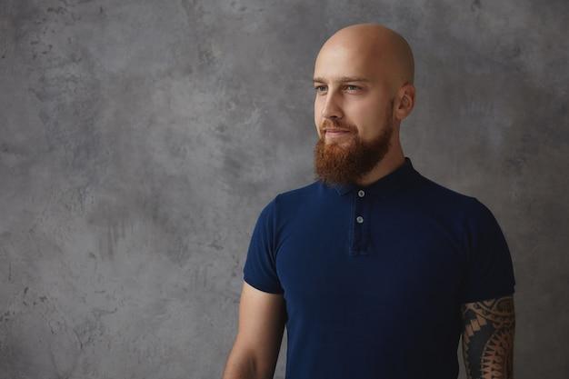Koncepcja ludzi, stylu i mody. stylowy przystojny młody mężczyzna rasy kaukaskiej z łysą głową i rozmytą brodą, stojący na białym tle przy pustej szarej ścianie copyspace, ubrany w modną koszulkę polo