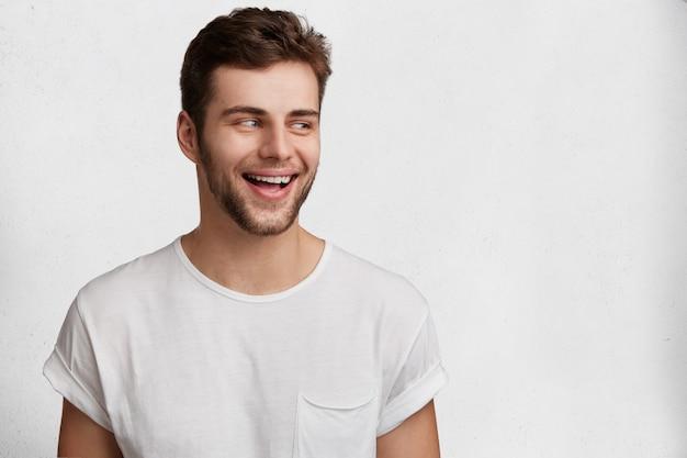Koncepcja ludzi, szczęścia i emocji. uśmiechnięty radosny młody mężczyzna o atrakcyjnym wyglądzie, ubrany w zwykłą białą koszulkę, radośnie patrzy na bok, pozuje na tle studia z miejscem na kopię
