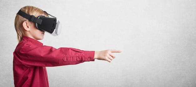 Koncepcja ludzi, technologii i postępu. mały podekscytowany chłopiec nosi futurystyczne okulary 3d, doświadcza wirtualnych rzeczywistości