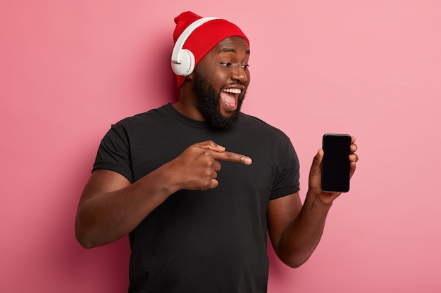 Koncepcja ludzi, technologii, stylu życia i reklamy. szczęśliwy ciemnoskóry mężczyzna pokazuje pusty ekran urządzenia smartphone