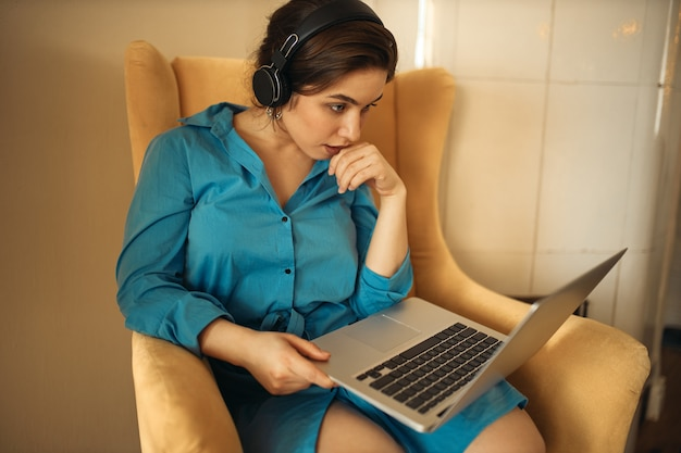 Koncepcja ludzi, technologii, uczenia się i edukacji. atrakcyjna, poważna młoda kobieta studiuje online, oglądając seminarium internetowe przy użyciu bezprzewodowego zestawu słuchawkowego, siedząc w fotelu z przenośnym komputerem na kolanach