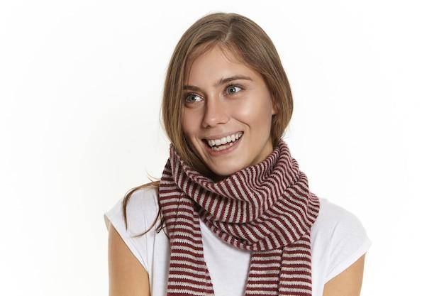 Koncepcja ludzi, ubrań, pory roku, stylu i mody. pojedyncze ujęcie wspaniałych stylowych młodych kobiet rasy kaukaskiej uśmiechnięta szczęśliwie, ubrana w białą koszulkę i długi szalik w paski na zimny jesienny dzień