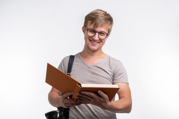 Koncepcja ludzi, wiedzy i edukacji - mężczyzna student czyta książkę na białej ścianie