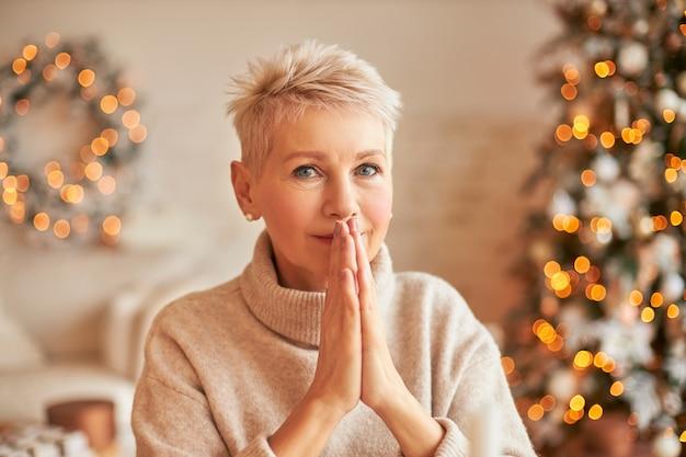 Koncepcja ludzi, wieku, stylu życia, celebratonu i wakacji. piękna dojrzała kobieta w beżowym kaszmirowym pulowerze, ściskająca dłonie, przewidująca wyraz twarzy, składająca życzenie w przytulnym salonie