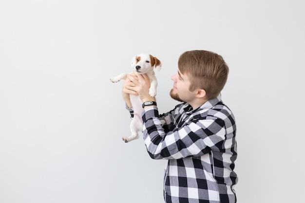 Koncepcja ludzi, zwierząt domowych i zwierząt - młody człowiek trzymający jack russell terrier szczeniaka na białej powierzchni