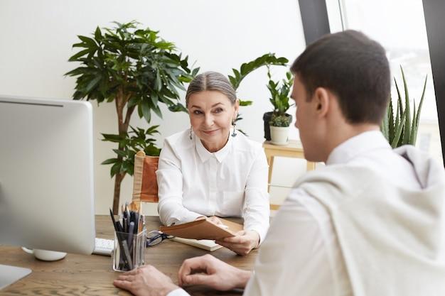 Koncepcja ludzie, biznes, praca, kariera i zatrudnienie. zdjęcie uśmiechniętego prezesa pięknej dojrzałej kobiety o spotkaniu z młodym menedżerem płci męskiej, omawiającej nowy projekt w lekkim nowoczesnym wnętrzu biurowym
