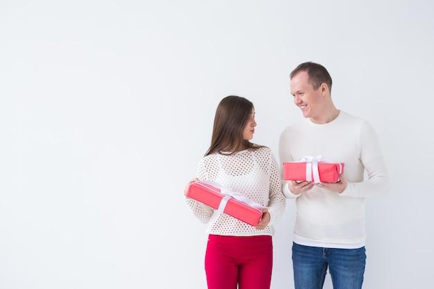 Koncepcja ludzie, boże narodzenie, urodziny, święta i walentynki - szczęśliwy młody mężczyzna i kobieta z pudełkami na białym tle z miejsca na kopię.