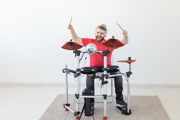 Koncepcja ludzie, czas wolny i hobby - fajny perkusista mężczyzna na białym tle pokoju