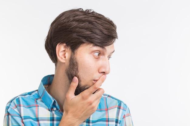 Koncepcja ludzie, emocje i gest - młody człowiek zaskoczony, zasłaniając usta ręką na białym tle.