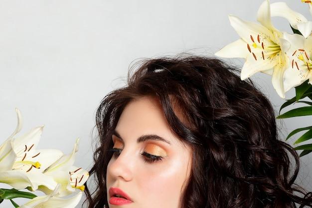 Koncepcja ludzie, emocje, naturalne, piękno, kwiaty i styl życia - piękna dziewczyna bierze piękne kwiaty w swoje ręce. dmuchający kwiat. fryzura z kwiatami. letni portret bajki. długie włosy po trwałej.