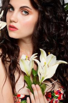 Koncepcja ludzie, emocje, naturalne, piękno, kwiaty i styl życia - piękna dziewczyna bierze w ręce piękne kwiaty. dmuchający kwiat. fryzura z kwiatami. letni portret bajki. długie włosy po trwałej.