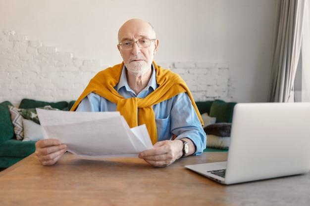 Koncepcja ludzie, finanse, technologia i praca. poważny modny emerytowany biznesmen robi finanse w nowoczesnym biurze, trzymając papiery w dłoniach, otwierając laptopa na drewnianym stole od niego