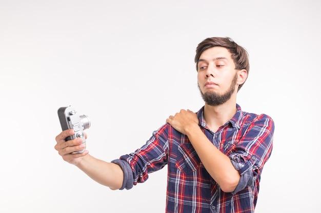Koncepcja ludzie, fotograf i gest - człowiek za pomocą staromodnego aparatu patrząc przez obiektyw na białej powierzchni