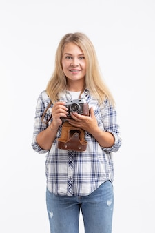 Koncepcja ludzie, fotograf i gest - kobieta za pomocą staromodnego aparatu na białym tle