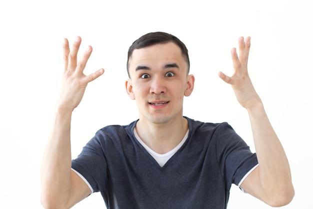 Koncepcja ludzie, gest i moda - podekscytowany zły człowiek azjatycki na białym tle nad białym