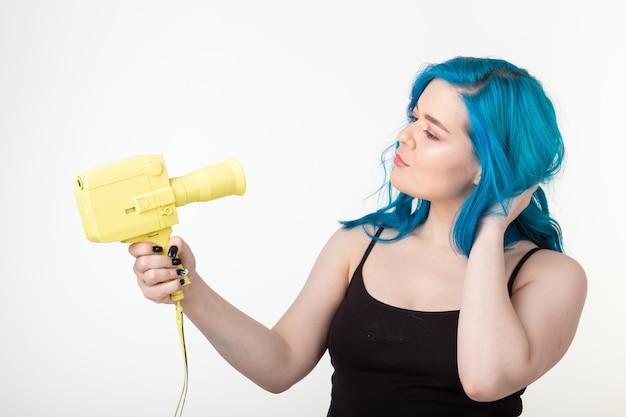 Koncepcja ludzie, hobby i moda - piękna dziewczyna z niebieskimi włosami trzyma żółty retro aparat na białym tle