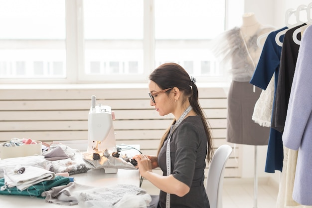 Koncepcja ludzie i moda - młoda kobieta krawcowa szyje ubrania na maszynie do szycia