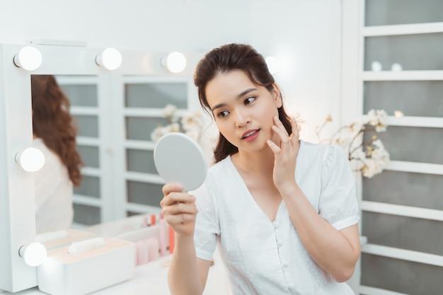 Koncepcja ludzie i uroda - piękna kobieta z lustrem dotykając jej skóry twarzy w sypialni w domu