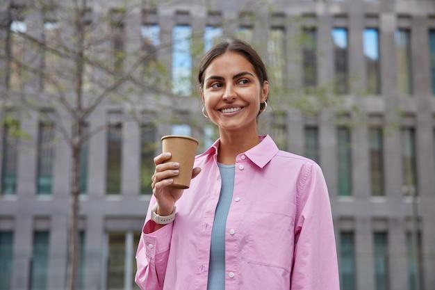 Koncepcja ludzie i wypoczynek. pozytywna młoda dziewczyna spaceruje po mieście, ma przerwę na spacer, cieszy się weekendową i dobrą wiosenną pogodą, pije kawę na wynos, nosi różową koszulę, pozuje w pobliżu budynku