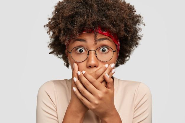 Koncepcja ludzie i zaskoczenie. zdumiona ciemnoskóra młoda kobieta ma wyskakujące oczy