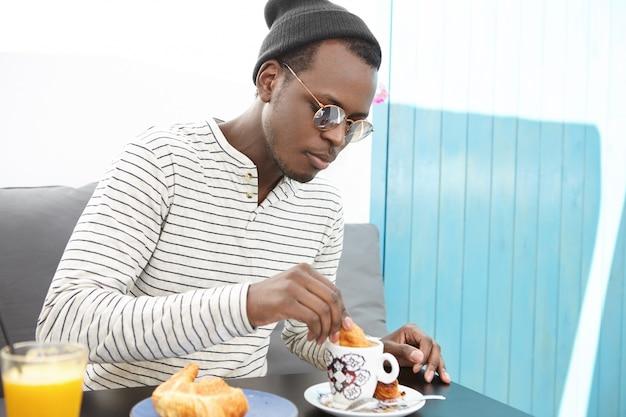 Koncepcja ludzie, jedzenie, wypoczynek i styl życia. przystojny modny afroamerykanin w modnych okularach i nakryciu głowy zanurza rogalika w kubku kawy, delektując się pysznym śniadaniem w kawiarni