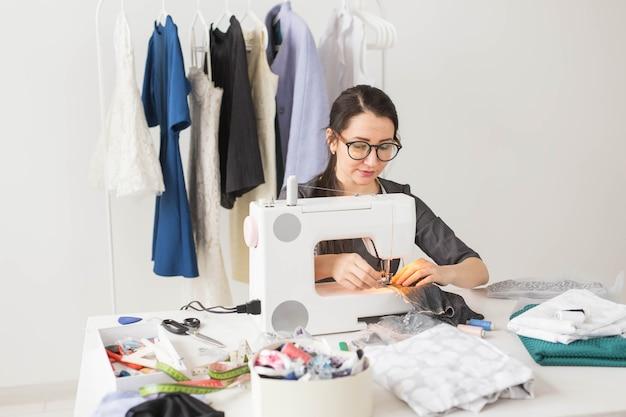 Koncepcja ludzie, krawcowa, krawiec i moda - młoda projektantka mody w swoim salonie.