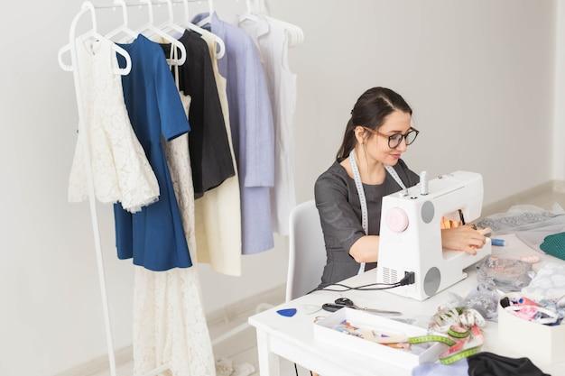 Koncepcja ludzie, krawcowa, krawiec, moda i showroom - młoda projektantka mody w swoim salonie.