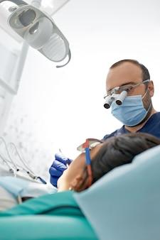 Koncepcja ludzie, medycyna, stomatologia i opieki zdrowotnej - zadowolony mężczyzna dentysta z pacjentem kobieta w biurze kliniki dentystycznej.