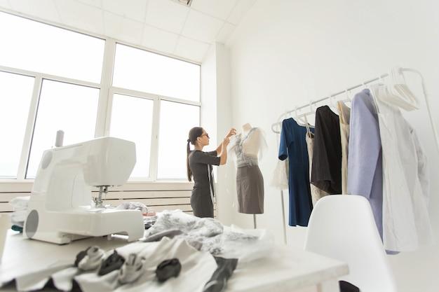 Koncepcja ludzie, moda i showroom - młoda projektantka mody w swoim salonie.