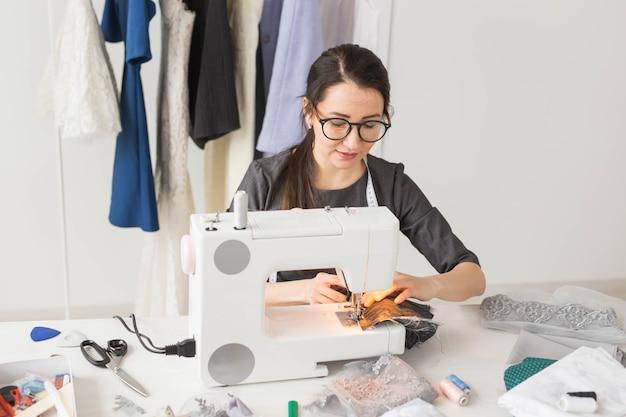 Koncepcja ludzie, moda i showroom - młody projektant mody szyje ubrania na maszynie do szycia.