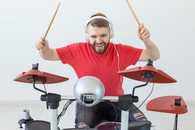 Koncepcja ludzie, muzyka i hobby - mężczyzna ubrany w czerwoną koszulkę grający na perkusji elektronicznej