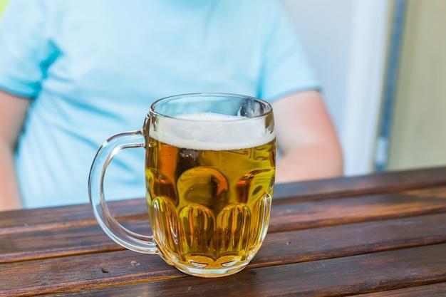 Koncepcja ludzie, napoje, alkohol, gest i rozrywka - bliska młody człowiek pije piwo.