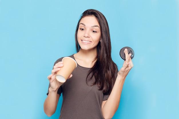 Koncepcja ludzie, napoje i styl życia - młoda piękna kobieta z kawą na niebieskim tle. szczęśliwa i uśmiechnięta atrakcyjna kobieta. kobieta o ciemnych włosach trzyma tekturową szklankę z kawą