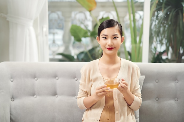 Koncepcja ludzie, napoje i wypoczynek - szczęśliwa młoda kobieta z filiżanką herbaty w domu