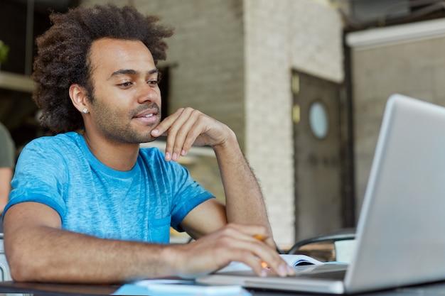 Koncepcja ludzie, nowoczesna technologia, edukacja, nauka i wiedza. przystojny, pewny siebie młody afro amerykanin siedzi przed otwartym laptopem, studiuje, bierze kurs online na temat sztuki współczesnej