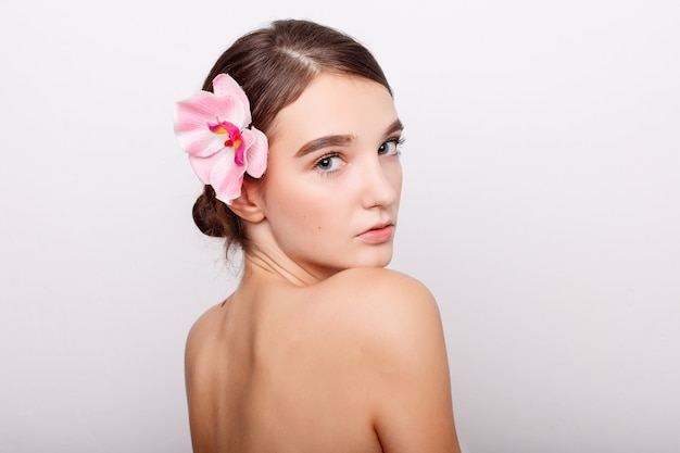 Koncepcja ludzie, odwodnienie, pielęgnacja skóry i uroda - piękna dziewczyna z orchidei flowers.beauty model twarz kobiety. idealna skóra. profesjonalny makijaż. piękna kobieta twarz zbliżenie portret ręce na skórze