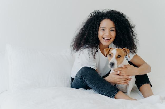 Koncepcja ludzie, opieka nad zwierzętami i przyjaźń. uśmiechnięta kobieta afro z radosnym wyrazem pieści rodowód psa, usiądź na wygodnym łóżku