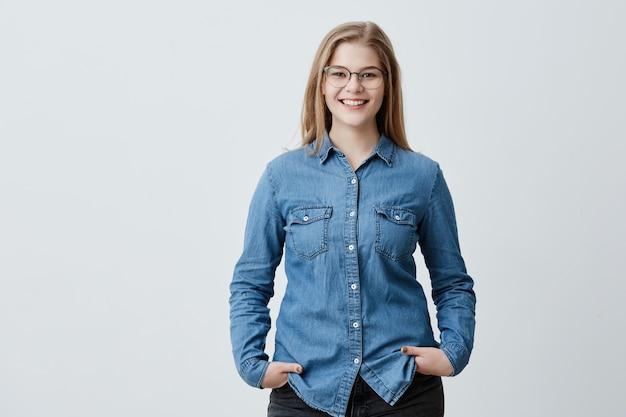 Koncepcja ludzie, piękno i styl życia. atrakcyjna zmysłowa blondynka z okularami i szerokim uśmiechem ubrana w dżinsową koszulę, uśmiechająca się szeroko, chętnie spotykająca się ze swoją najlepszą przyjaciółką. radosna miła kobieta