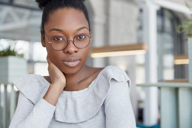 Koncepcja ludzie, pochodzenie etniczne i mimika. pewna kobieta w okularach, na co dzień, poważnie słucha partnera